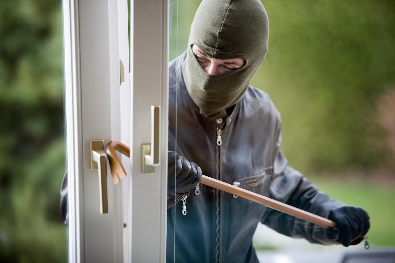 Einbrecher dringt in ein Haus ein.